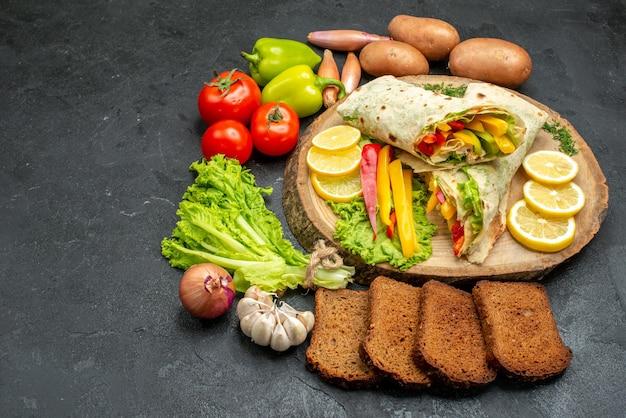 Vooraanzicht gesneden heerlijke shaurma vleessandwich met brood en groenten op donkere ruimte