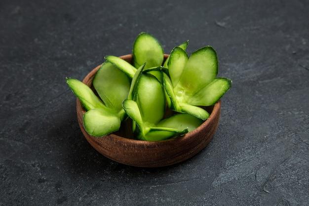 Vooraanzicht gesneden ontworpen komkommers in pot op grijze ruimte