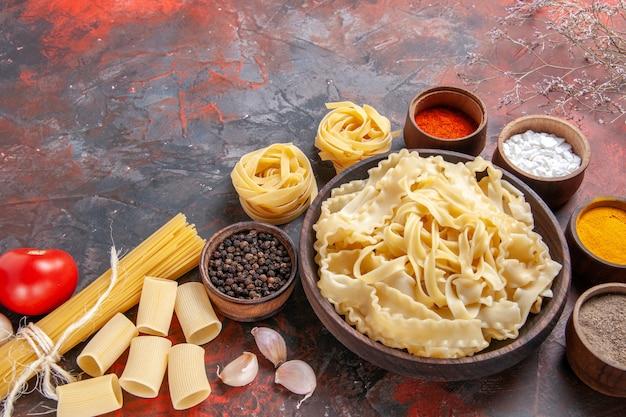 Vooraanzicht gesneden rauw deeg met kruiden op donkere oppervlak pasta deeg donker voedsel