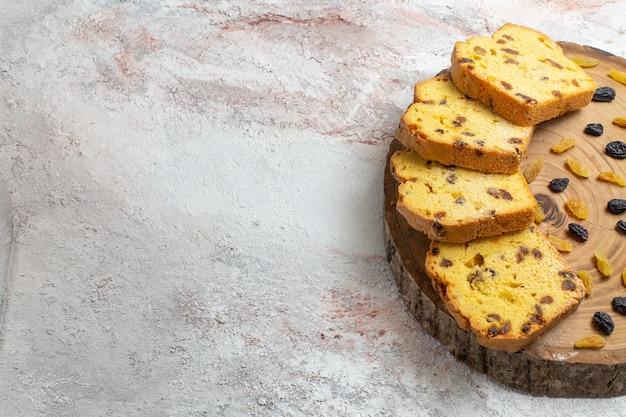Vooraanzicht gesneden rozijnencake met verse rozijnen op het lichtwitte bureau