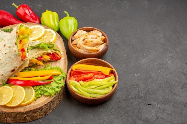 Vooraanzicht gesneden shaurma vleessandwich met schijfjes citroen en groenten op donkere ruimte