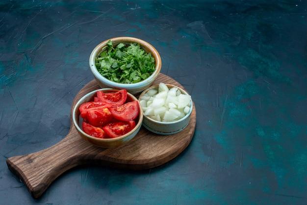 Vooraanzicht gesneden verse groenten, tomaten en uien met greens op donkerblauwe het dinergroenteschotel van het bureauvoedsel