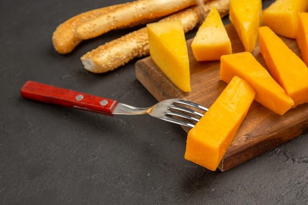 Vooraanzicht gesneden verse kaas met broodjes op donkere kleurenfoto snackmaaltijd ontbijt knapperig