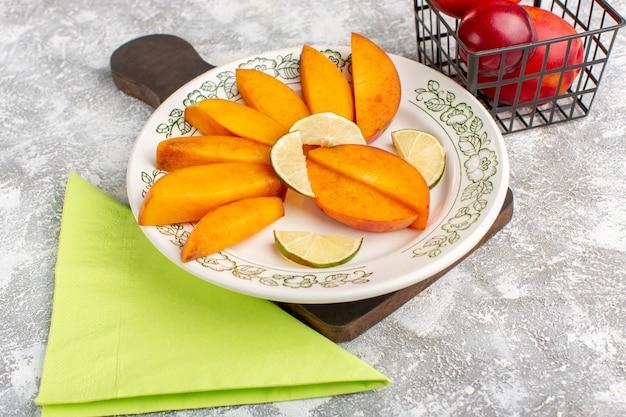 Vooraanzicht gesneden verse perziken binnen plaat met citroenen op lichte witte vloer vers perzik fruit zacht sap