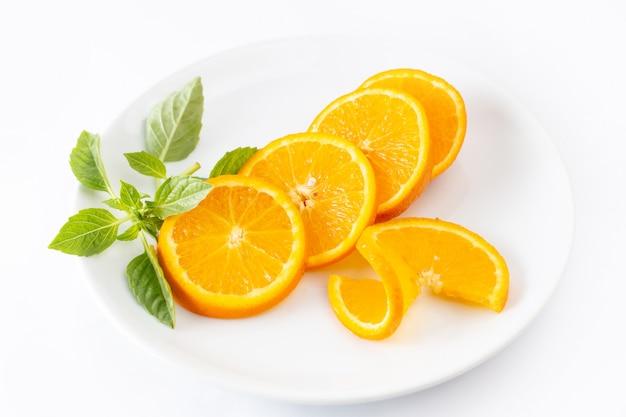 Vooraanzicht gesneden verse sinaasappelen in witte plaat op wit