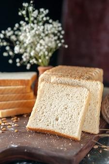 Vooraanzicht gesneden wit brood op donkere achtergrond broodje deeg bakkerij thee ontbijt brood ochtend gebak