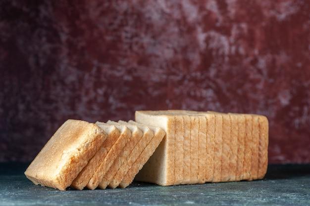 Vooraanzicht gesneden wit brood op donkere achtergrond thee ontbijt deeg gebak bakkerij broodje cake bak ochtendbrood