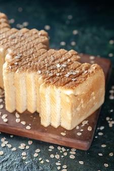 Vooraanzicht gesneden wit brood op een donkere achtergrond thee ontbijt eten gebak broodje ochtendbrood bakkerij deeg