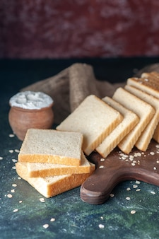 Vooraanzicht gesneden wit brood op een donkere achtergrond thee ontbijt eten gebak ochtendbrood bakkerij deeg broodje