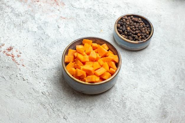 Vooraanzicht gesneden wortelen met peper op witte ruimte