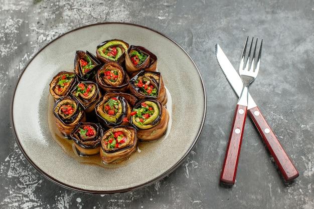Vooraanzicht gevulde auberginebroodjes in witte plaat gekruiste vork en mes op grijs