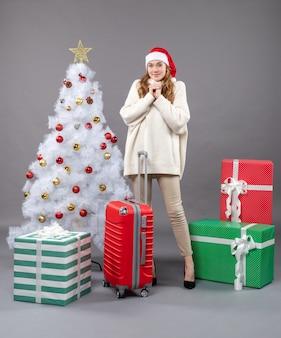 Vooraanzicht gezegend meisje met kerstmuts staande in de buurt van witte kerstboom en kleurrijke geschenkdozen