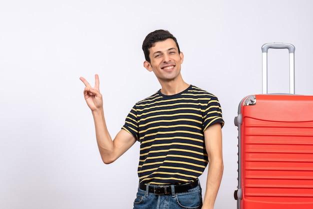 Vooraanzicht gezegende jonge man met gestreept t-shirt overwinningsteken maken