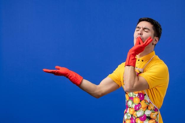 Vooraanzicht gezegende mannelijke huishoudster in schort die hoofdkusteken maakt making