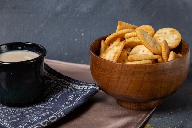 Vooraanzicht gezouten chips met zwarte kop melk op grijs