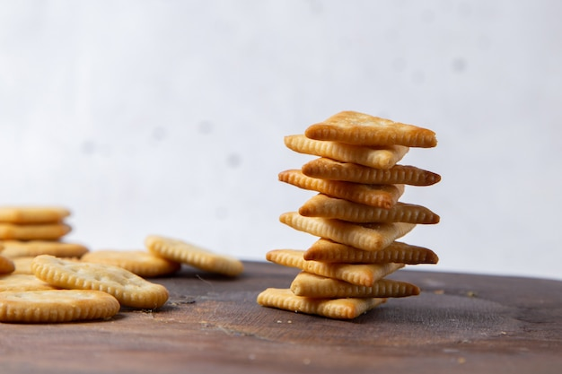 Vooraanzicht gezouten smakelijke chips bekleed op houten bureau en lichte cracker knapperige snack