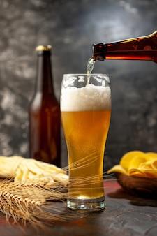 Vooraanzicht glas beer met cips fles en kaas op licht bureau wijn foto alcohol drinken snack kleur