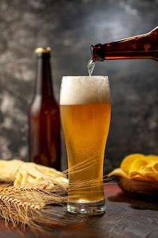 Vooraanzicht glas beer met cips fles en kaas op lichte wijn foto alcohol drinken snack kleuren
