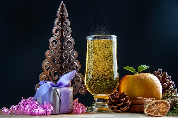 Vooraanzicht glas champagne met kegels appel en cadeautjes op donkere kleur drankje party