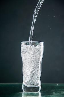 Vooraanzicht glas frisdrank dat op de donkere drank wordt gegoten foto champagne kerst water