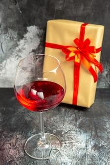 Vooraanzicht glas wijn cadeau op donker