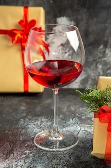 Vooraanzicht glas wijn geschenken op donkere achtergrond