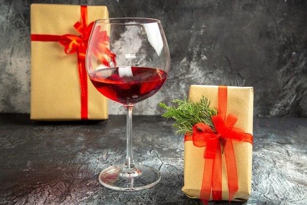 Vooraanzicht glas wijn kerstcadeaus op donker