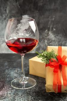 Vooraanzicht glas wijn kerstcadeaus op donkere achtergrond