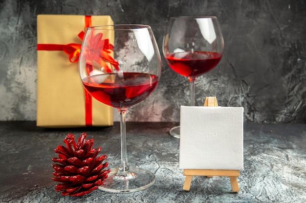 Vooraanzicht glazen wijn kerstcadeau wit canvas op houten ezel dennenappel op donker