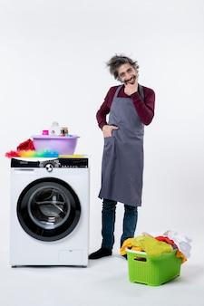 Vooraanzicht glimlachende huishoudster man in schort staande in de buurt van witte wasmachine op witte muur