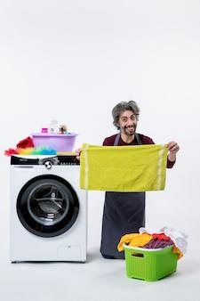 Vooraanzicht glimlachende huishoudster man staande op de knie met groene handdoek op witte muur