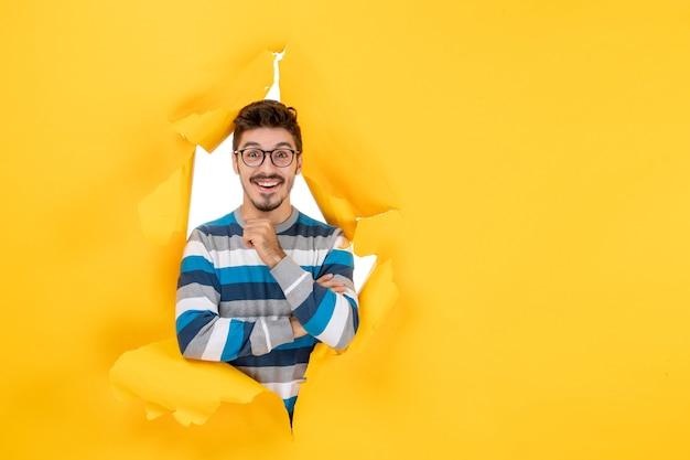 Vooraanzicht glimlachende jonge man die door gele muur van gescheurd papier kijkt