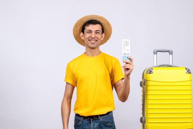 Vooraanzicht glimlachende jonge toerist die zich dichtbij het gele kaartje van de kofferholding bevindt