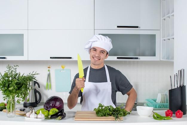Vooraanzicht glimlachende mannelijke chef-kok in uniform met mes in de keuken