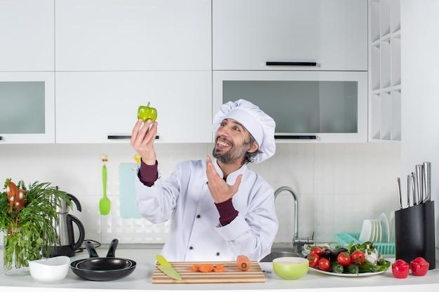 Vooraanzicht glimlachende mannelijke kok in uniform die groene peper in de keuken omhoog houdt