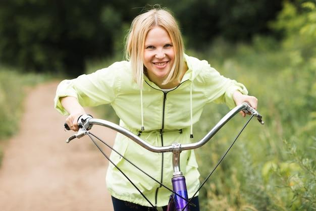 Vooraanzicht glimlachende vrouw op fiets