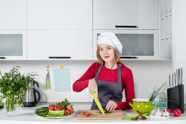 Vooraanzicht glimlachende vrouwelijke kok in schort die komkommer snijdt