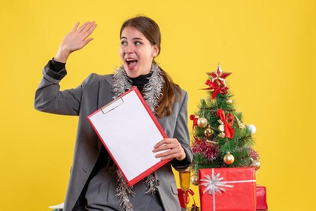 Vooraanzicht glimlachte meisje met documenten die iemand begroeten die zich dichtbij kerstmisboom en giftencocktail bevindt