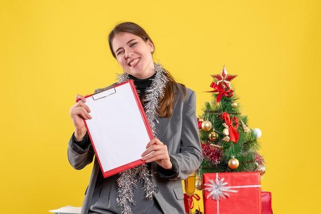 Vooraanzicht glimlachte meisje met documenten die zich dichtbij kerstmisboom en giftencocktail bevinden