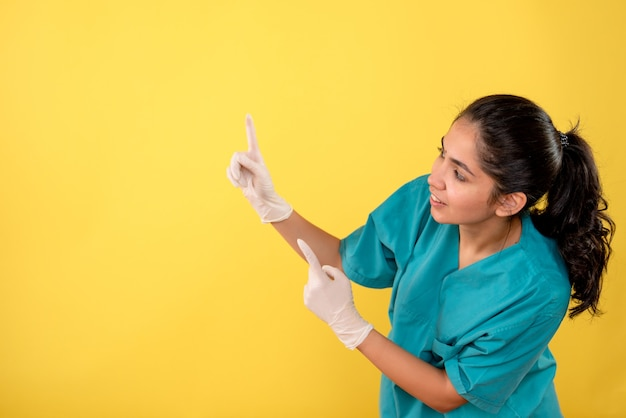 Vooraanzicht glimlachte vrouwelijke arts met latexhandschoenen die met vinger omhoog op gele achtergrond wijzen