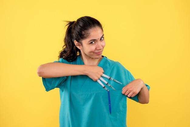 Vooraanzicht glimlachte vrouwelijke arts met spuiten in de hand staande op gele achtergrond