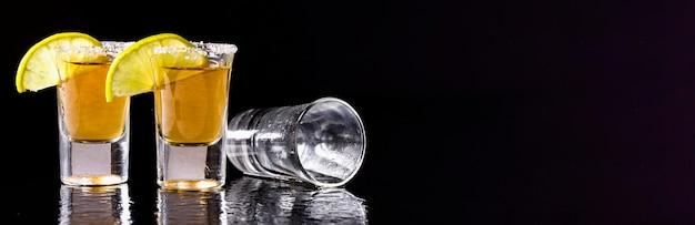 Vooraanzicht gouden tequila shots met limoen met kopie-ruimte