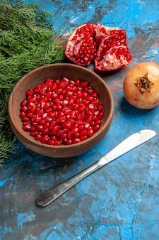 Vooraanzicht granaatappel zaden in kom diner mes een gesneden granaatappel op blauw