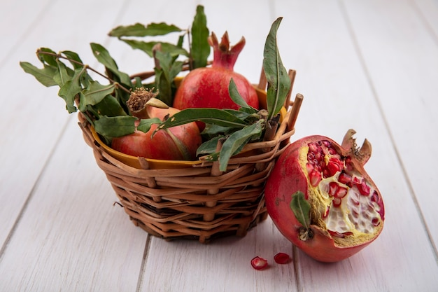 Vooraanzicht granaatappels met takken van bladeren in een mand op een witte achtergrond