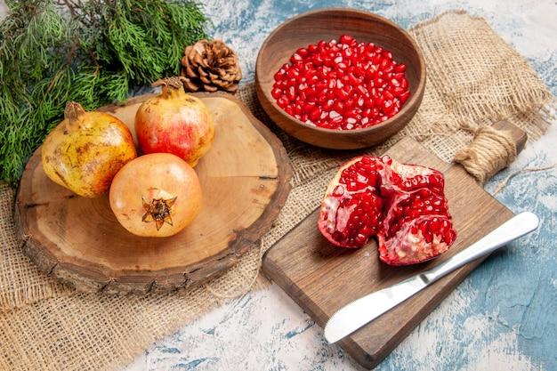 Vooraanzicht granaatappels op ronde snijplank granaatappel zaden in kom een gesneden granaatappel op snijplank pijnboomtak op blauw-witte achtergrond
