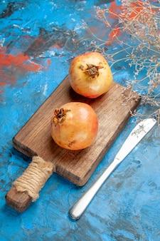Vooraanzicht granaatappels op snijplank dinermes op blauw
