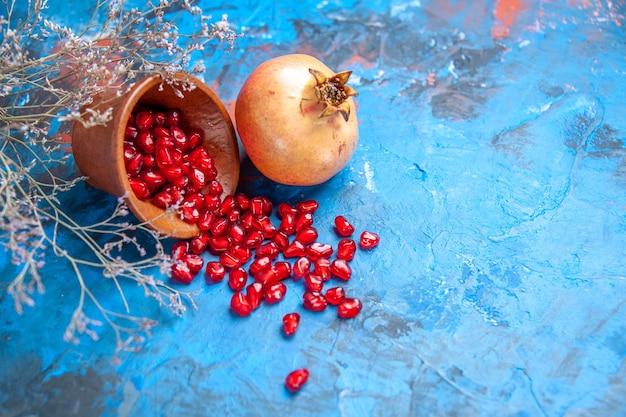 Vooraanzicht granaatappelzaden in houten kom een granaatappel gedroogde wilde bloemtak op blauwe vrije plaats