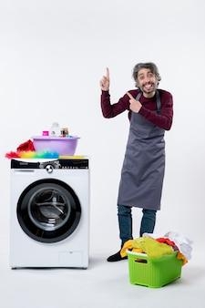 Vooraanzicht grappige huishoudster man wijzend op plafond staande in de buurt van wasmachine wasmand op witte achtergrond