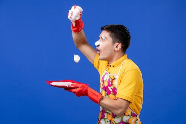 Vooraanzicht grappige huishoudster met schuim op zijn gezicht knijp spons op blauwe ruimte