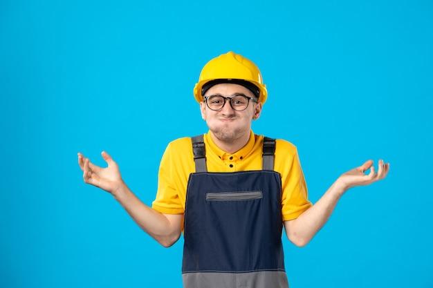 Vooraanzicht grappige mannelijke bouwer in uniform en helm verward op blauw